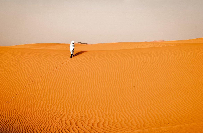 Caminhando na areia das Dunas de Erg Chebbi, Saara, Marrocos.