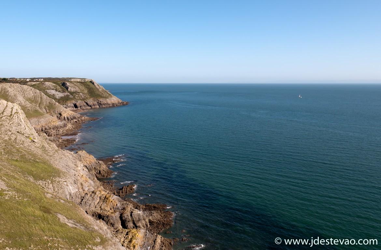 Um barco navega pela costa do País de Gales, Gower Peninsula
